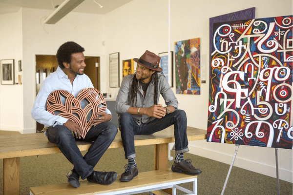 Trevor Parham and Abba Yahudah with their respective artwork, featured at Oakstop.